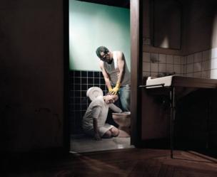 رجل يجبر امرأة على وضع يدها في مرحاض