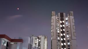 Superlua azul é vista perto de prédios modernos em Cingapura