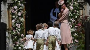 The Duchess of Cambridge stands with the page boys and bridesmaids outside church