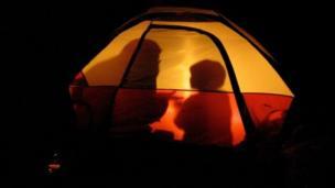 Sombras de madre e hijo acampando.