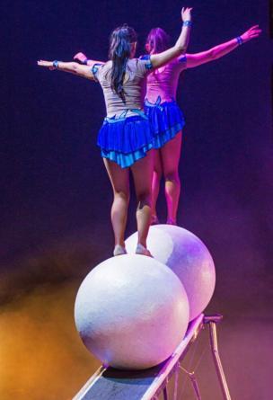 Two girls balance on a ball
