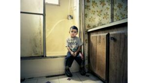 Niño sentado en el borde de una ducha.