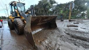 A bulldozer clears mud off the road near a flooded section of US Highway 101 near the San Ysidro exit in Montecito, California.