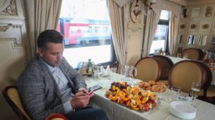 Un hombre revisa su teléfono celular frente a una mesa de uno de los restaurantes en el tren Zarengold.