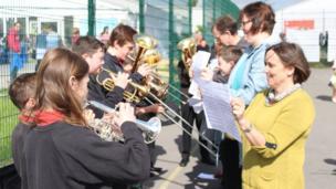 Band pres Ysgol Penweddig yn ymarfer ar yr iard chwaraeon