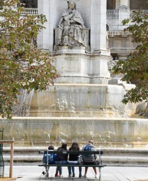 Estudiantes al pie de una estatua.