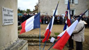 "People gather during the unveiling of a plaque at the ""monument aux morts "" in memory of Chloe Boissinot, in Chateau-Larcher, central France, a victim of an attack on the Parisian restaurant ""Le Petit Cambodge"" one of several venues attacked by terrorists in Paris on November 13, 2015, as the French nation marks Armistice Day commemorations on November 11."