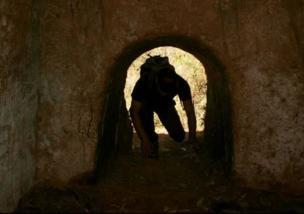 Un turista se arrastra por un túnel en El Salvador