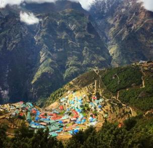 Es una ciudad con techos azules sobre una montaña verde vista desde muy arriba. Cerca donde está el Everest.