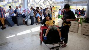 A child sits on top of luggage on a trolley as tourists queue to leave Lombok Island