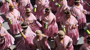 Dancers in pink shawls and bowler hats perform
