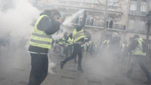 Image shows a protester throwing a tear gas canister.
