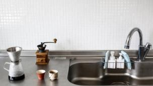 Cups sit beside the kitchen sink in the home of minimalist Naoki Numahata