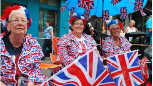 Rachel, Linda and Agnes are each dressed in union jack t-shirts, jumpers and trousers, and holding union jack flags