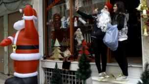 Suriyeli genç kızlar ülkenin kuzeyindeki Kamışlı kentinde Noel eşyaları satan bir dükkanın önünde özçekim yapıyorlar