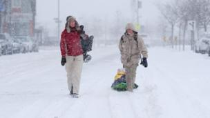 dua orang tengah berjalan di atas salju