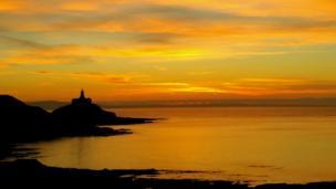 An amber sunrise over Mumbles Lighthouse