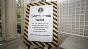 A sign in the West Wing reads: 'Construction alert: This is an active work site. For your safety, please stay clear from the West Wing.'