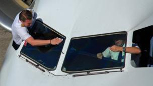 विमान की खिड़की साफ करने पायलट