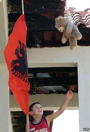 Child reaches up to a teddy bear from a balcony