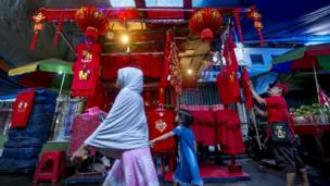 People walk past a kiosk selling Chinese-style decorations and T-shirts for the Lunar New Year in Jakarta on February 16, 2018