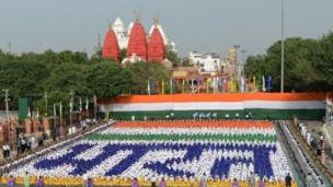 As India dey celebrate their 71st Independence Day, them arrange their national flag colour near wall of the Red Fort.