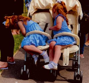 Twin girls in matching blue dresses lean over to retrieve their snacks at the bottom of the buggy