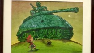 صورة لطفل يلعب الكرة أمام دبابة