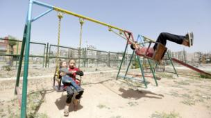 Children play on swings in Douma, 20 April