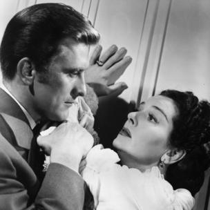 Actress Rosalind Russell fends off the advances of her admirer Kirk Douglas, in the film Mourning Becomes Electra.