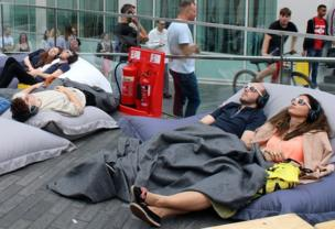 People relax on beanbags in the centre of a busy city