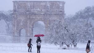 Tourists visit the Arch of Constantine during a snowfall in Rome