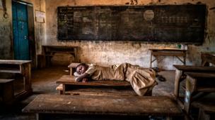 Una niña duerme en un pupitre en una escuela con escasos recursos