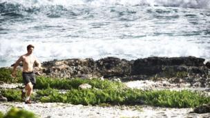 Joven corriendo en la playa en Isla Mujeres, México