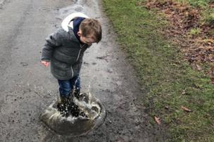 Boy jumping in a hole filled with water