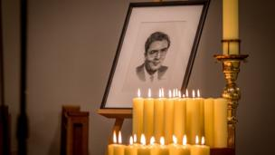 A portrait of John Hume surrounded by candles lit by members of his family and colleagues