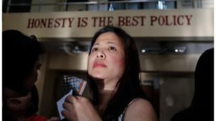 "A woman's face as she stands in a queue before sunrise, to cast her vote inside a school polling station in Makati city, south of Manila. On the outside of the school is written ""honesty is the best policy"""