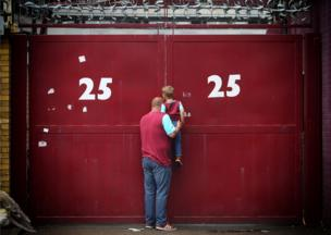 A father lifts his son up to look through a gap in the gates of Upton Park as West Ham United play their last game at Upton Park, against Manchester United.