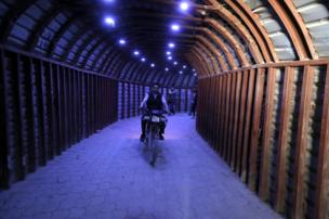 A man rides a motorcycle in a tunnel in Douma, Syria, 20 April 2018
