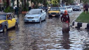 أمرأة تسير في شارع غمرته مياه الأمطار في مدينة الإسكندرية الساحلية شمالي مصر