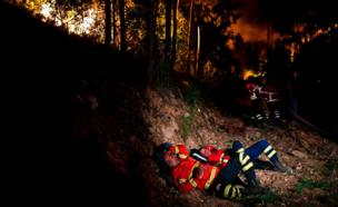 Firefighters rest during a wildfire at Penela, Coimbra, central Portugal, on 18 June, 2017.