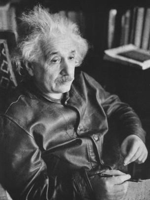 Einstein sentado, usando uma jaqueta de couro, com cabelo bagunçado e olhar distante