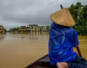 A man paddles through the flooded streets of Hoi An, Vietnam