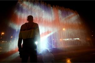 A man stands in front of a fountain illuminated with the colours of the United Kingdom flag in Zagreb, 23 May