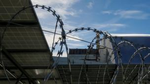 Solar panels are seen through barbed wire in front of the New Safe Confinement arch covering the damaged fourth reactor of the Chernobyl nuclear power plant in Ukraine on 5 October 2018