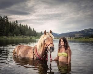 Джессіка стоїть у воді з її конем