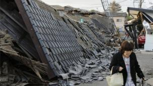 A resident walks past collapsed houses in Mashiki, Kumamoto prefecture, southern Japan, Friday, April 15, 2016,