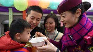 中國高鐵的乘務員在一列列車上為旅客送上湯圓,歡度佳節
