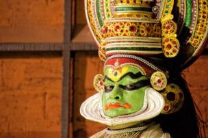 A performer is covered in green face paint with detail around their eyes and forehead. They are also wearing a jewelled headpiece