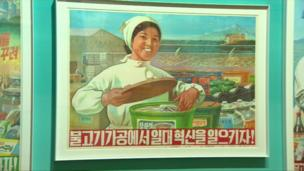 A printed poster saying 'Let's innovate the fish industry!' Fishing is a dominant industry of the North Korean economy. (1981)